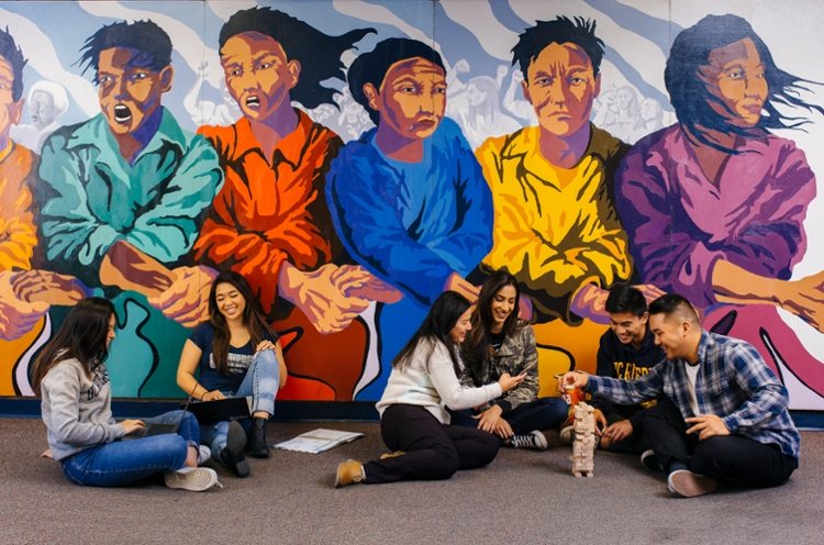 UC Riverside students sitting in front of mural